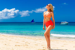 Young beautiful girl in bikini is standing on the beach. Blue tr Stock Photo