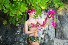 Young beautiful girl in a bikini stands of tropical flowers Royalty Free Stock Photography