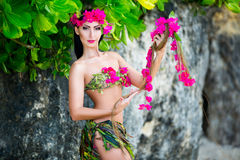 Young beautiful girl in a bikini stands of tropical flowers stock images