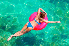 Young beautiful girl in bikini swims in a tropical sea on a rubber ring. Summer vacation concept. royalty free stock photography