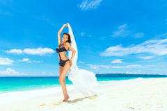 Young beautiful girl in bikini with white cloth on the beach of Royalty Free Stock Photography