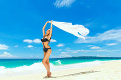 Young beautiful girl in bikini with white cloth on the beach of Royalty Free Stock Photo