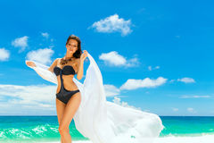Young beautiful girl in bikini with white cloth on the beach of Royalty Free Stock Photos