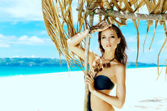 Young beautiful girl in bikini with white cloth on the beach of Stock Photography