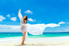 Young beautiful girl in bikini with white cloth on the beach of Stock Images