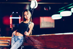 Young beautiful girl in a billiard club, with cue stick posing Royalty Free Stock Images