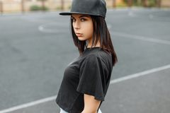 Young beautiful girl in a black baseball cap and t-shirt on the. Background of the stadium royalty free stock photography