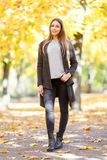 A beautiful girl in a black coatis on the blurred background of autumn park. Young beautiful girl in a black coat on autumn background with yellow leaves Stock Photography