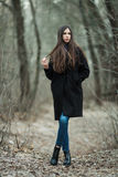 Young beautiful girl in a black coat blue scarf exploring autumn / spring forest park. An elegant brunette girl with gorgeous extr Royalty Free Stock Images
