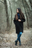 Young beautiful girl in a black coat blue scarf exploring autumn / spring forest park. An elegant brunette girl with gorgeous extr Stock Photo