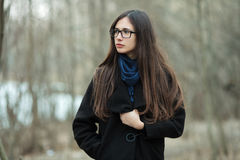 Young beautiful girl in a black coat blue scarf glasses exploring autumn / spring forest park. An elegant brunette girl with gorge Royalty Free Stock Photography