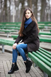 Young beautiful girl in a black coat blue scarf glasses sitting on bench in city park. An elegant brunette girl with gorgeous extr Royalty Free Stock Images