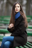 Young beautiful girl in a black coat blue scarf glasses sitting on bench in city park. An elegant brunette girl with gorgeous extr Stock Photography