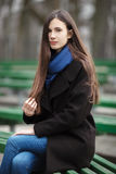 Young beautiful girl in a black coat blue scarf glasses sitting on bench in city park. An elegant brunette girl with gorgeous extr Stock Image