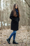 Young beautiful girl in a black coat blue scarf glasses walking in the autumn / spring forest park. An elegant brunette girl with Stock Photos
