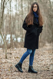 Young beautiful girl in a black coat blue scarf glasses walking in the autumn / spring forest park. An elegant brunette girl with Royalty Free Stock Photography