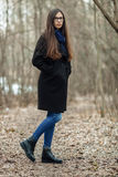 Young beautiful girl in a black coat blue scarf glasses walking in the autumn / spring forest park. An elegant brunette girl with Stock Image