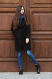 Young beautiful girl in a black coat and blue scarf having fun. Elegant brunette girl with gorgeous extra long hair against wooden. Doors. Lifestyle concept Stock Images