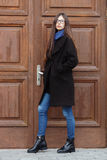 Young beautiful girl in a black coat and blue scarf having fun. Elegant brunette girl with gorgeous extra long hair against wooden. Doors. Lifestyle concept Royalty Free Stock Images