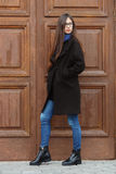 Young beautiful girl in a black coat and blue scarf having fun. Elegant brunette girl with gorgeous extra long hair against wooden. Doors. Lifestyle concept Stock Image