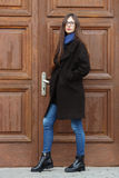 Young beautiful girl in a black coat and blue scarf having fun. Elegant brunette girl with gorgeous extra long hair against wooden. Doors. Lifestyle concept Stock Photos