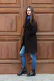 Young beautiful girl in a black coat and blue scarf having fun. Elegant brunette girl with gorgeous extra long hair against wooden. Doors. Lifestyle concept Royalty Free Stock Photography