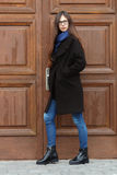 Young beautiful girl in a black coat and blue scarf having fun. Elegant brunette girl with gorgeous extra long hair against wooden. Doors. Lifestyle concept Stock Photo