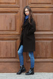 Young beautiful girl in a black coat and blue scarf having fun. Elegant brunette girl with gorgeous extra long hair against wooden. Doors. Lifestyle concept Stock Photography