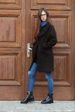 Young beautiful girl in a black coat and blue scarf having fun. Elegant brunette girl with gorgeous extra long hair against wooden. Doors. Lifestyle concept Royalty Free Stock Image