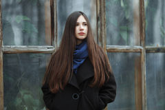 Young beautiful girl in a black coat and blue scarf for a posing in the autumn / spring park. An elegant brunette girl with gorgeo. Us extra long hair. Lifestyle Royalty Free Stock Photos