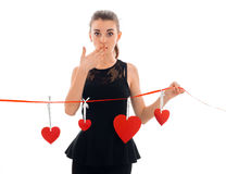 Young beautiful girl in black dress covers her mouth and hand holds a Red Ribbon with hearts. Isolated on white background Stock Image