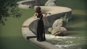 Young beautiful girl in black dress plays violin staying on bridge outdoors stock video footage