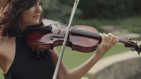 Young beautiful girl in black dress plays violin staying on bridge outdoors. Elegant brunette violinist in forest. Art conception in 4k close up stock video