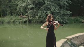 Young beautiful girl in black dress plays violin staying on bridge outdoors stock video