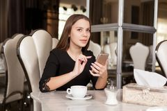 The girl in the cafe. Young beautiful girl in black dress sits in a cafe and drinks coffee stock photos
