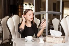 The girl in the cafe. Young beautiful girl in black dress sits in a cafe and drinks coffee stock image