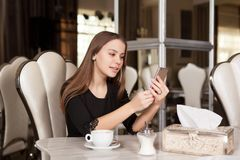 The girl in the cafe. Young beautiful girl in black dress sits in a cafe and drinks coffee stock photo