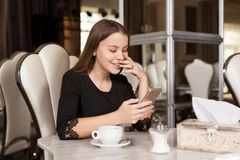 The girl in the cafe. Young beautiful girl in black dress sits in a cafe and drinks coffee royalty free stock images