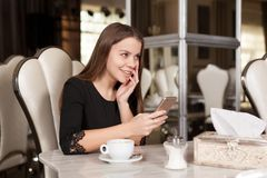 The girl in the cafe. Young beautiful girl in black dress sits in a cafe and drinks coffee royalty free stock photos