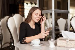 The girl in the cafe. Young beautiful girl in black dress sits in a cafe and drinks coffee royalty free stock image