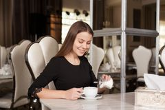 The girl in the cafe. Young beautiful girl in black dress sits in a cafe sugar pours and drinks coffee stock photo