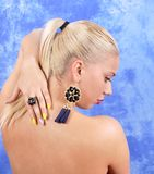 Young beautiful girl in black earrings on an abstract background Stock Photos