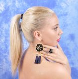 Young beautiful girl in black earrings on an abstract background Royalty Free Stock Images