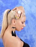 Young beautiful girl in black earrings on an abstract background Stock Photo