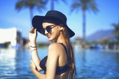 Young beautiful girl in black fashion hat smile, velvet skin, red lips, black swimsuit posing in the pool in blue water. Stylish sunglasses, glamor, outdoor Royalty Free Stock Image