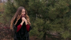 Young beautiful girl in a black fur coat on background of trees. stock video