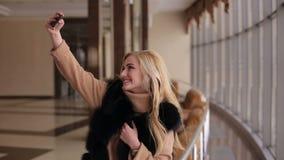 Girl in the fur coat takes a selfie in hotel lobby stock video
