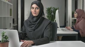 Young beautiful girl in black hijab typing on laptop, looking at camera and talking, speaking. 60 fps. 4k stock footage