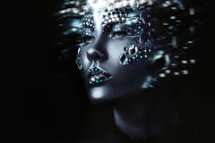 Young beautiful girl in black makeup with rhinestone, dark background, motion effect Royalty Free Stock Photo