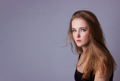 Young, beautiful girl in a black t-shirt. Professional model posing in Studio on white-gray background. Take a model test Royalty Free Stock Photo